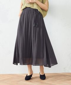 《素材》<br>レーヨン・ナイロンの柔らかな楊柳素材です。<br>楊柳ならではの縦方向の凹凸感が強調され、すっきりとした印象。<br>また、生地の凹凸感により肌の接地面が減り、清涼感があります。<br>《デザイン》<br>自然なフレアを出す、ギャザースカート。<br>ロング丈ですが、素材の軽さや清涼感があり、軽やかな印象。<br>共布の紐ベルト先にはタッセルを付け、リゾート感をプラスしました。<br>ウエストは1周ゴム仕様で、ストレスのない履き心地です。