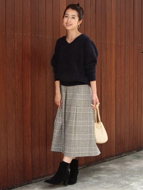 季節感あふれる毛足の長いニットにトレンドのチェック柄のミドル丈スカートをあわせたスタイル。