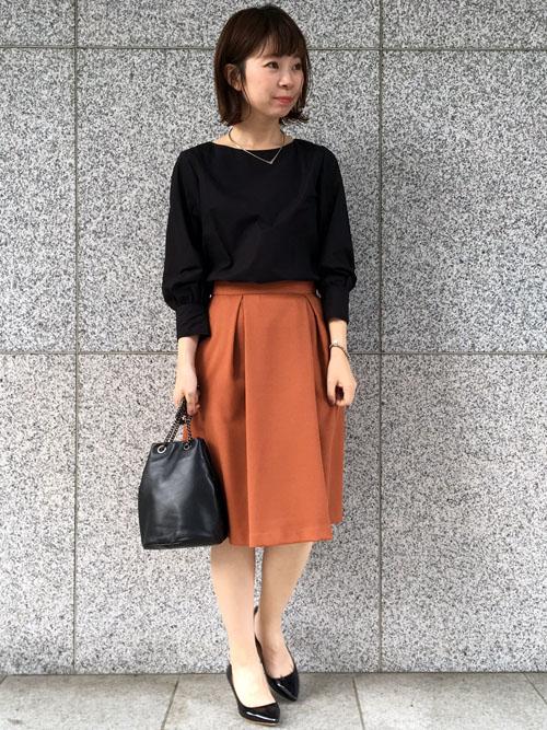 """『鮮やかなカラーのスカートが主役の通勤スタイル 』  トップスや小物は、ブラックで統一して大人っぽく仕上げました。 カフスにあしらったゴールドボタンやボリュームスリーブは注目の""""袖コンシャス""""。オフィスでも取り入れやすい旬なディテールです。   【スタッフ着用レビュー】  ■普段のサイズ:Sサイズ  ■身長:159cm  ■着用感:ブラウスの袖の長さは短めですが、ボリュームが少しあります。首元はボートネックのようなデザインが上品な印象です。着丈は少し短めで裾のラウンドがアウトでもサマになります。 スカートは程よいタックで広がり過ぎないシルエットです。膝下丈でオフィススタイルにもぴったり。  ■生地感:ブラウスは少しハリのあるのコットン素材。スカートはしっかりとした厚みのある生地で温かみもあります。"""
