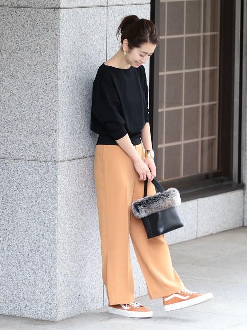 秋らしいオレンジ系カラーのパンツやスニーカーでまとめたスタイル。