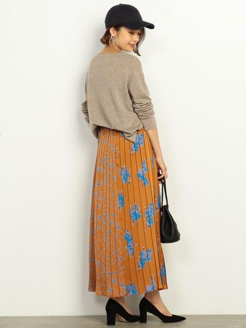 華やかなフラワープリントを施したプリーツスカートが主役のスタイル。