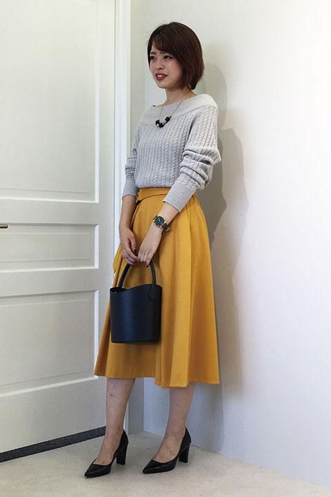 細かなケーブル編みのオフショルダーニット×イエローのひざ下スカートでクラシカルな雰囲気に。贅沢なタック使いのスカートは腰回りをカバーしてくれる優れもの。