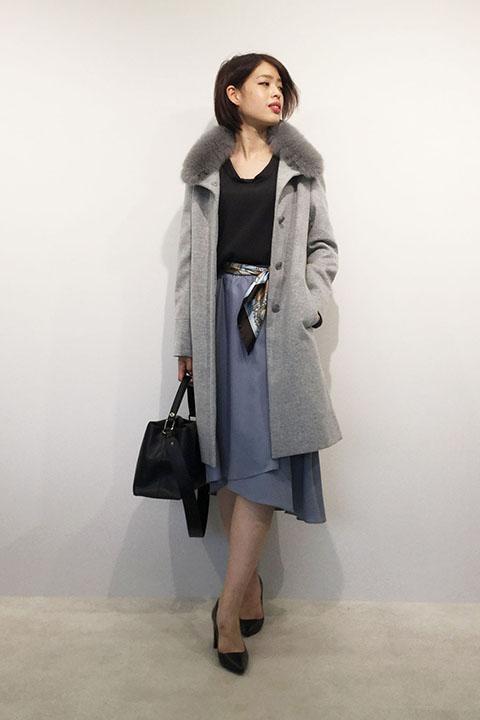 1枚持っていると便利なファー付きスタンドカラーコートと、グレーと相性の良い淡いブルーのスカートにはポイント使いでスカーフベルトを。年末の華やかスタイルに。