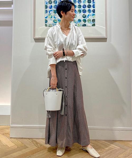 上質な光沢としっとりとしたタッチが魅力のブラウスは、ネックラインのフリルとギャザーがポイント。 自然なボリュームあるブラウスに落ち感のあるGANNIのスカートを合わせて、大人なまとまりあるスタイルに。