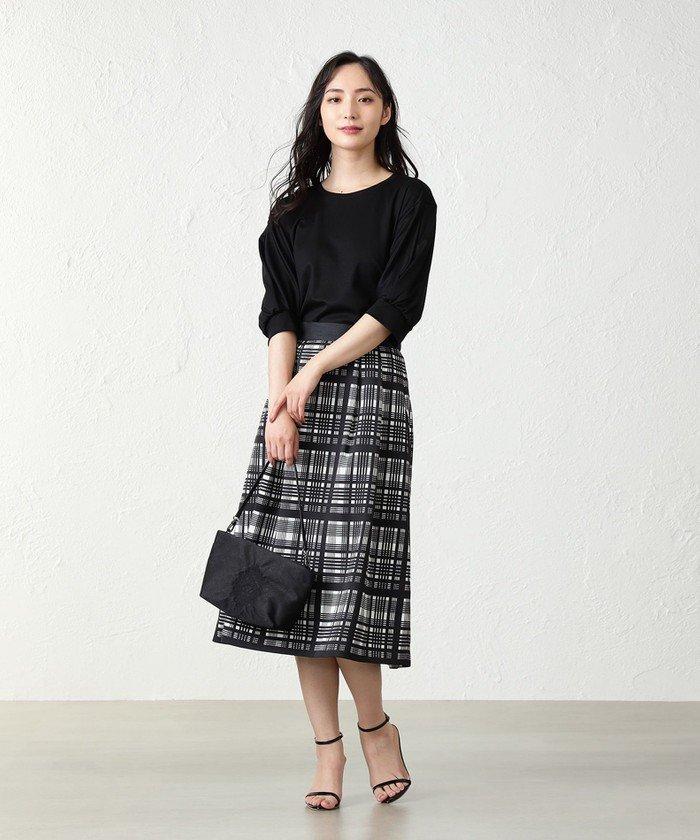 袖口がエレガントなトップスと大きな格子柄が全体にプリントされているスカートを黒でまとめたスタイリング。