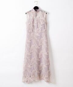"""モンステラなどの大胆なリーフモチーフが刺繍されたコードレースドレス。<br />柄を一から緻密に計算し作り上げた、こだわりが詰まった美しいレースが最大の特徴。<br />ボディラインを美しく見せる縦長の美シルエットと、今年らしいハイネックが女性らしさを漂わせます。<br />大人の女性が品よく着こなせるよう長めのシルエットと露出度を控えめに仕上げたデザインがポイント。<br />""""Grace Class""""ならではの、色気と品格を感じさせる特別な一日に相応しい一着です。<br />グレイッシュラベンダーとインナーに配色カラーを入れて柄を際立たせたブラックの2色をご用意しました。<br />"""