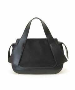 大人フェミニンなリボン調に仕立てた持ち手とラウンドシルエットが女性らしいハンドバッグ。牛革とナイロンを異素材ジョイントさせた立体的で個性あふれるひと品です。ファスナー間口でしっかりと留められ、十分な収納力でお出かけに最適。色の濃淡も面白いオススメのコンパクトバッグです。