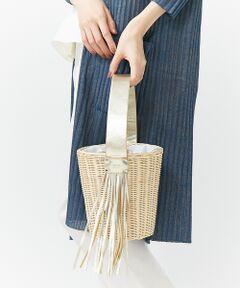 アシンメトリーにフリンジをあしらったラタン編みのバケツ型バッグ。<br>長さのあるフリンジが揺れてポイントに。<br>巾着になっている中生地にはトロピカルなボタニカル柄を取り入れ季節感満載。<br>デイリーからリゾートまで、夏のお出かけにぴったりなアイテムです。<br><BR>