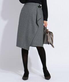 ■デザイン<br />シンプルなハウンドトゥース柄(千鳥柄)を、絶妙なカラーミックスで表現した、J.PRESSオリジナル柄のラップスカート(巻きスカート)です。<br />前左側のラップ部分の下に落ちるラッフル感は、歩くとさりげなく揺れる女性らしいディティール。<br />サイドにあしらったベルトは、生地の重さにより下がらないよう、内縫いして安定させています。<br />ウエストはジャストウエストで着用でき、トップスをインにした今年らしいコーディネートもキマりやすいシルエットです。<br />細かい柄なので無地感覚でお使いいただけ、スタイリングしやすいアイテムになっています。■素材<br />滑らかな肌触りと、上品な膨らみのある素材です。■着こなしポイント<br />すっきりシルエットのスカートなので、トレンドのボリューム袖トップスをインしてもバランスよく着こなせます。<br />柄スカートですが、無地感覚でお使いいただけるため、ボーダーやフェアアイルなどの柄ニットとも相性抜群です。■同素材アイテム<br />・ブラウス(BLGJYW0040)<br />大きいサイズ(BLGTYW0040)<br />小さいサイズ(BLG0YW0040)<br />・ワイドパンツ(PRGJYW0040)<br />大きいサイズ(PRGTYW0040)<br />小さいサイズ(PRG0YW0040)※商品画像はサンプルを使用しているため、色味やサイズ等の仕様に変更がある場合がございますので、予めご了承ください。
