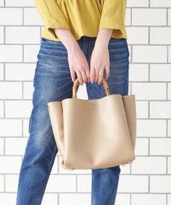 定番のバンブーハンドルトートバッグ。<br>前後に付いた大きめポケットで荷物をすっきり収納出来、<br>ショルダーベルトで斜めがけも出来る2WAYデザインは、<br>荷物の多くなるお仕事や旅行にぴったりで幅広く活用して頂ける使いやすいバッグです。<br>*摩擦や水濡れによる色落ち・色移行にご注意下さい。<br>*デリケートな素材を使用しておりますのでお取扱いにご注意下さい。