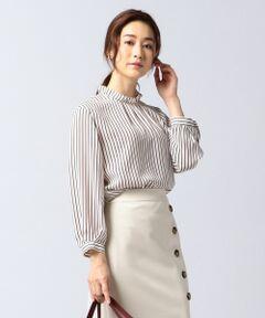 1枚でも着映えする、今年らしい雰囲気の大人なフリル衿ブラウス<br /><br />■デザイン<br />シンプルなダブルストライププリントなので、フリル衿でも甘すぎない、今期らしい雰囲気のブラウスです。パフスリーブで袖にボリュームがあり、一枚でも着映えします。カフスボタンが共地くるみ釦でポイントにしています。通勤ジャケットのインナーや、着流しカーディガンやスエードのインナーとして、オンオフ問わず、着用頂ける汎用性の高い一枚です。<br /><br />■素材<br />薄手でありながら透けないことが特徴で、適度な落ち感とドレープ性を備えた素材です。プリント後の仕上げで、ヴィンテージ加工と柔軟加工を行うころで生地に膨らみがあるのが特徴となっています。<br /><br />※画像はサンプルを使用している為、実際にお届けする商品と仕様やサイズが異なる場合がございます。